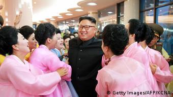 Kim Jong Un umgeben von einer Gruppe Frauen, die ihn anhimmeln