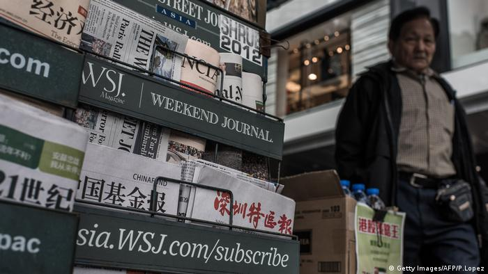 A man walks past a newspaper kiosk in Hong Kong on January 12, 2015