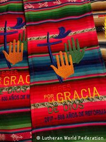 Mãos bordadas em laranja e verde com uma cruz em azul sobre pano listrado vermelho, azul e verde