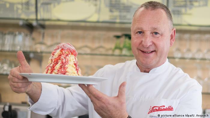 Dario Fontanella, the inventor of spaghetti ice cream, holding up a portion of spaghetti ice cream (picture-alliance /dpa/U. Anspach)