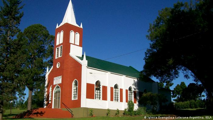 Igreja com torre nas cores vermelho e branco, situada entre várias árvores