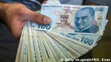 A change office staff shows Turkish lira on his hand on December 2, 2016 in Istanbul. Turks have over the past three months nervously watched the steady decline in value of the Turkish lira against the dollar, seeing it haemorrhage more than 10 percent in the past month alone. / AFP / OZAN KOSE (Photo credit should read OZAN KOSE/AFP/Getty Images)