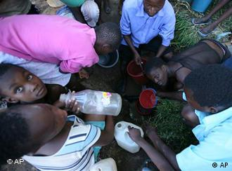 Women and children wait to collect water from an underground source following a water cut in Harare, Monday, Dec. 1, 2008. Water in the capital Harare was cut due to shortage of purification chemicals as Zimbabwe battles with a cholera outbreak which is thought to have left at least 425 people dead.(AP Photo/Tsvangirayi Mukwazhi)