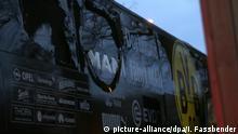 Der Bus von Borussia Dortmund steht mit einer beschädigten Scheibe am 11.04.2017 in Dortmund (Nordrhein-Westfalen) an einer Straße. Kurz nach der Abfahrt der Mannschaft von Dortmund vom Hotel zum Stadion sind in der Nähe des Mannschaftsbusses drei Sprengsätze explodiert. Das teilte die Polizei in Dortmund am Dienstagabend mit. Der BVB-Bus wurde nach Vereins-Angaben an zwei Stellen beschädigt. BVB-Spieler Bartra ist bei der Explosion verletzt worden. Foto: Ina Fassbender/dpa +++(c) dpa - Bildfunk+++ | Verwendung weltweit