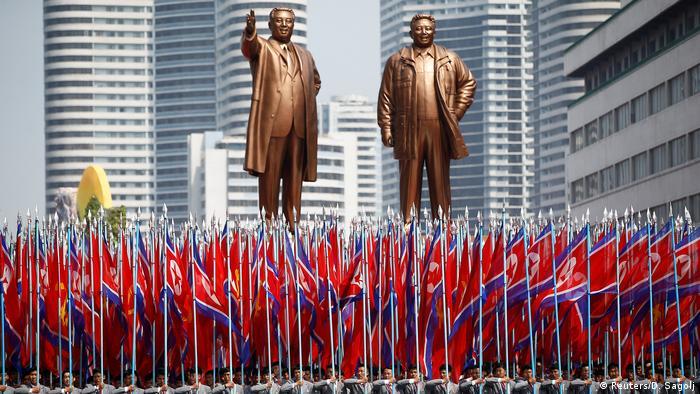 Soldaten mit nordkoreanischen Flaggen vor den riesigen Statuen von Kim Il Sung und Kim Jong Il