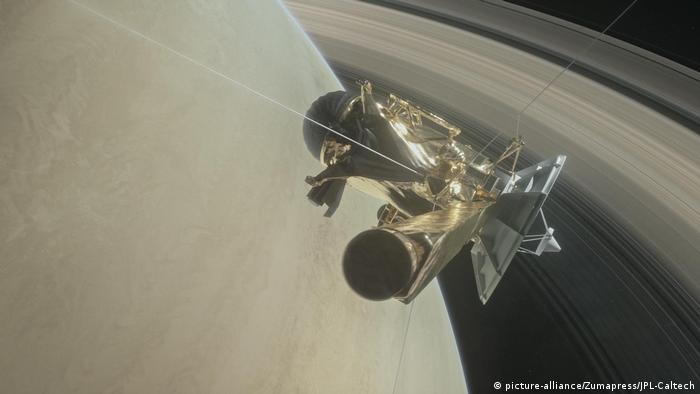 An illustration of the Cassini space probe diving between Saturn's rings.