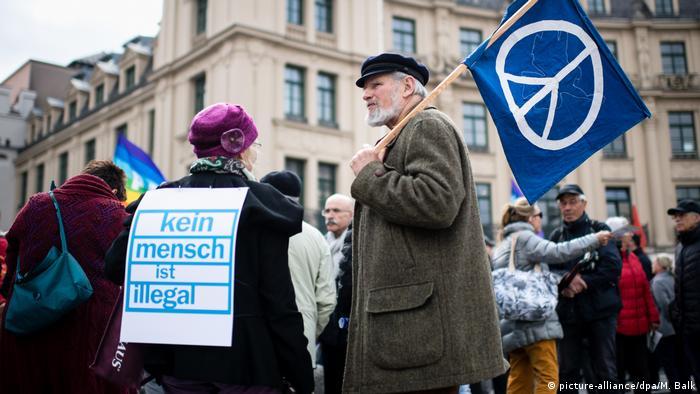 Frau mit Kein Mensch ist illegal-Schriftzug auf dem Rücken, daneben ein Mann mit Peacefahne beim Ostermarsch in München. (picture-alliance/dpa/M. Balk)