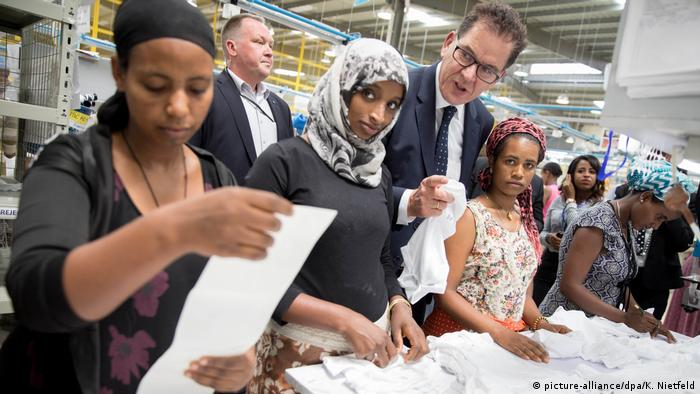 German development minister Gerd Müller (standing, right) talks to women working at a textile factory in Ethiopia
