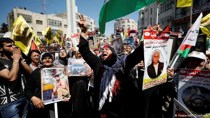 Frauen halten die Bilder von Inhaftierten in die Höhe (Foto: Reuters)