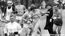 ARCHIV- Kathrine Switzer mit der Nummer 261 aus Syracuse (N.Y.) kämpft sich am 21.04.1967 beim Boston Marathon an Marathon-Direktor Bill Cloney (im schwarzen Mantel) vorbei. 1967 setzte Kathrine Switzer eine Revolution im Sport im Gang: Als erste Frau lief und beendete sie den Boston-Marathon. Foto: UPI/dpa (zu dpa-Korr.: «Nach Boston-Schock: Frauenlauf-Pionierin Switzer wirbt in Berlin» vom 03.05.2013) +++(c) dpa - Bildfunk+++ |