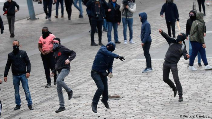 Masked demonstrators throw stones outside the venue of a campaign rally for Marine Le Pen, French National Front (FN) candidate for the election. Paris, April 17.