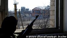 FEBRUARY 28, 2017: DONETSK REGION, UKRAINE - FEBRUARY 28, 2017: A man with a rifle in a window of a house in the village of Kominternovo after a shelling attack. Viktor Drachev/TASS |