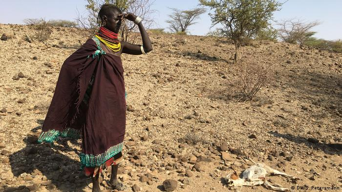 A Turkana pastoralist next to one of her goats that failed to suvrive the drought