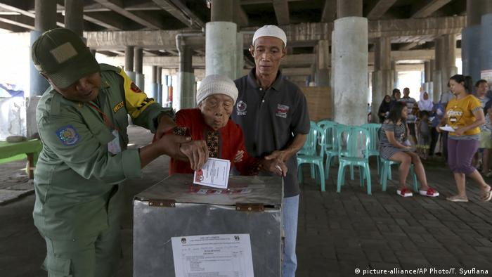Electoral workers help an elderly woman cast her ballot