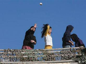 A Jewish settler throws a stone from a rooftop overlooking Palestinian houses in the West Bank city of Hebron, Tuesday, Dec. 2, 2008. Dozens of Jewish settlers rioted Tuesday in the West Bank town of Hebron, clashing with the Israeli troops who guard them but who may also soon evict them from a disputed building they've occupied. (AP Photo/Nasser Shiyoukhi)