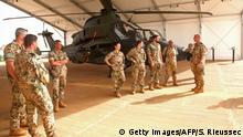 07.04.2017 German soldiers stand near a helicopter at the MINUSMA (United Nations Multidimensional Integrated Stabilization Mission in Mali) base in Gao on April 7, 2017. Germany said on April 7, 2017, the US air strike on a Syrian airbase was understandable following a suspected chemical attack on a rebel-held town but urged a political solution to the conflict. The fact that the United States has now reacted with a strike against military sites of the Assad regime, from which this cruel war crime was perpetrated, is understandable, said Foreign Minister Sigmar Gabriel. His French counterpart Jean-Marc Ayrault, with Gabriel on a trip to Mali, said he hoped the strikes would show Syria's allies Russia and Iran that they should withdraw their support for Assad. / AFP PHOTO / Sebastien RIEUSSEC (Photo credit should read SEBASTIEN RIEUSSEC/AFP/Getty Images)