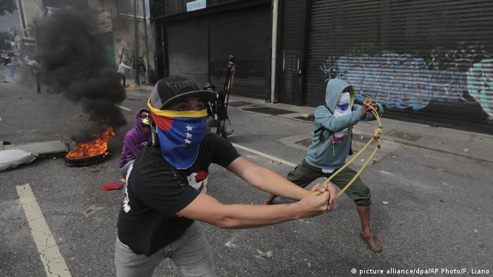 Демонстранты бросают камни в сотрудников полиции, Каракас, 19 апреля 2017 г.