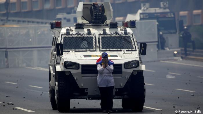 Одна из участниц акции протеста стоит перед правительственным бронетранспортером, переграждая ему дорогу