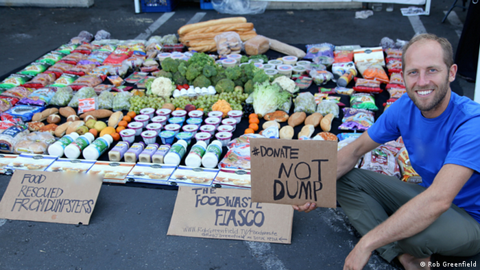 A man sits next to food he rescued from a dumpster