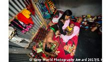 """Erster Platz im Wettbewerb Tägliches Leben, Fotografin: Sandra Hoyn, Deutschland. Image Name: 9 Photographer Name: Sandra Hoyn Year: 2017 Image Description: <p>Kajol with her 6-month-old baby Mehedi and a customer on her bed. Two weeks after birth of Mehedi she was forced to have sex again with customers. Because of the baby her business is not good.</p> Series Name: The Longings of the Others Series Description: The Kandapara brothel in the district of Tangail is the oldest and one of the largest in Bangladesh - it has existed for some 200 years. It was demolished in 2014 but has been re-established with the help of local NGOs. The brothel district is surrounded by a two-metre wall, and in the narrow streets within, there are food stalls, tea shops and street vendors. More than 700 sex workers live and work here with their children and their madams. Many of the women were either trafficked or born inside the brothel's walls and in this way their livelihood is secure. Their customers are policemen, politicians, farmers, fishermen, factory workers and groups of teenage boys. The brothel is a place with its own rules and power hierarchies, which are completely different from mainstream society. The most vulnerable stage is when a young sex worker enters the brothel, when she is called a bonded girl. Officially, sex workers must be 18 years old, but most are underage and bonded girls are usually 12 to 14 years old. They have no freedom or rights; they belong to a madam, have debts and are not allowed to go outside or keep their money. From the moment a woman has paid her debts, she is free to leave. Although prostitution inside registered brothels has been legal in Bangladesh since 2000, these women are socially stigmatised outside their """"homes"""" and thus often choose to stay and continue supporting their families with their earnings. Copyright: © Sandra Hoyn, Germany, 1st Place, Professional, Daily Life, 2017 Sony World Photography Awards"""