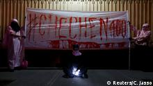 Activists from the group Chok3 stand next to a banner painted with their own blood during a protest against the constant discrimination and violence against the gay community in Chechnya and other regions of Russia, outside the Russian embassy in Mexico City, Mexico April 20, 2017. REUTERS/Carlos Jasso