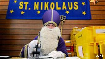 Der Nikolaus aus der saarlaendischen Gemeinde St. Nikolaus, Rudolf Lange, stempelt bei der Eroeffnung des Sonderpostamtes mit dem Nikolaus-Sonderstempel der Post. Quelle: ap
