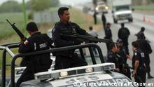 Mexican police holding guns in the back of a truck