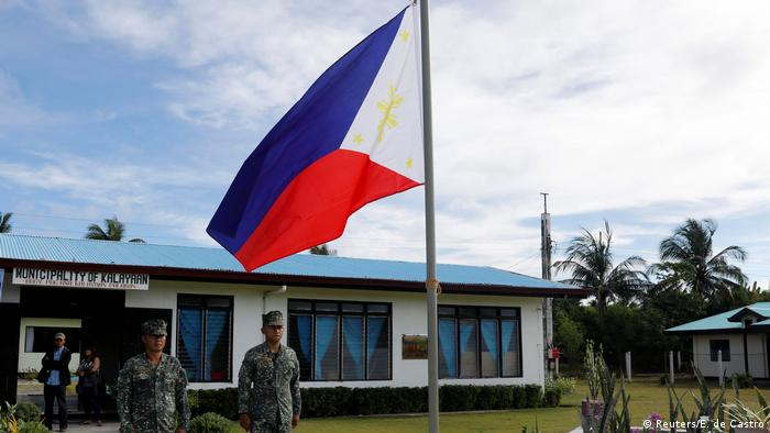 Filipino soldiers standing at attention by a Philippine flag in Thithu Island in the disputed South China Sea