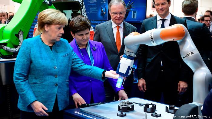 Angela Merkel loking at robotic arm at Hannover Fair