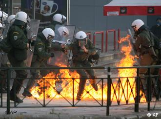 Riot police try to avoid a petrol bomb during clashes in central Athens on Sunday, Dec. 7, 2008.
