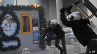 Protesters throw chair and fire bombs to riot police during clashes in the northern port city of Thessaloniki, Greece, on Sunday, Dec. 7, 2008.