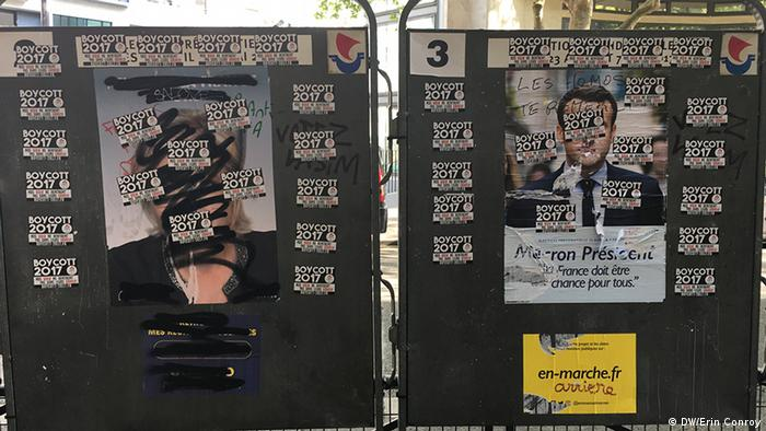 Posters of Le Pen and Macron defaced by stickers that call for a boycott of the election