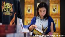 A customer reads a copy of 'Harry Potter and the Cursed Child' on the day of its release at a bookstore in Hong Kong on July 31, 2016. 'Harry Potter and the Cursed Child', the script book of the play of the same name by JK Rowling, writer Jack Thorne and director John Tiffany, is set 19 years after the seventh and final book in the Harry Potter series, 'The Deathly Hallows'. Rowling's books have sold more than 450 million copies of Harry Potter since 1997 and been adapted into eight films. / AFP / Anthony WALLACE (Photo credit should read ANTHONY WALLACE/AFP/Getty Images)