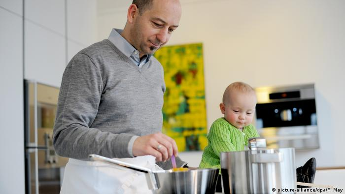 Men cooking with baby