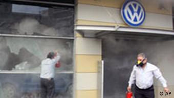 Owners of a Volkswagen dealership try to extinguish a fire during clashes in central Athens on Sunday, Dec. 7, 2008.
