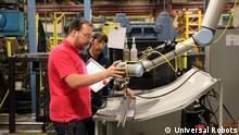 Werker in einer Fabrik in Kanada arbeiten gemeinsam mit einem Roboter