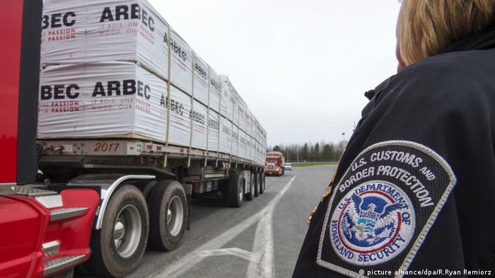 Тяжелый грузовик, груженый древесиной, пересекает границу США и Канады