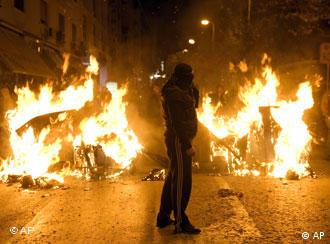 Rioting youth stands by a burning barricade in the center of Athens