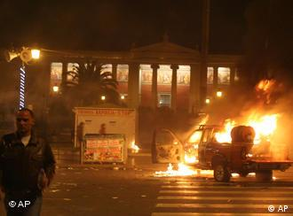 A vehicle burns outside the Athens University main building in central Athens.