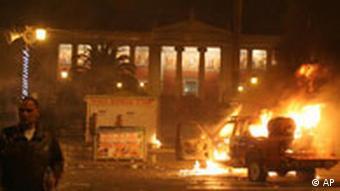 A car burns outside Athens University