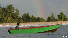 Tenene, on his way to fish for tuna, is seen in his boat, near Funafuti, Tuvalu, March 24, 2004. Tuvaluans still subsist in traditional ways: men in little skiffs fishing for tuna; families cultivating breadfruit and pulaka, a taro-like plant; coconut harvested to export its oil. (AP Photo/Richard Vogel)