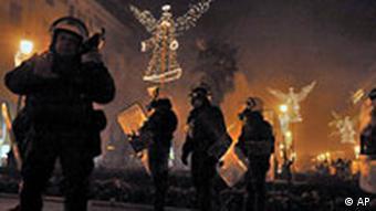 Policajci u tami s kacigama, iza njih požari