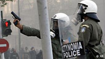 A riot police officer points at demonstrators with his gun