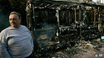 A man stands next to a burned bus ticket booth in central Athens