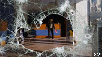 A woman, seen through a shattered storefront, clears debris inside a riot-damaged travel agency