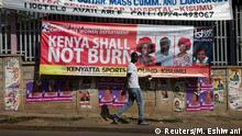 Man walks past a banner saying Kenya shall not burn
