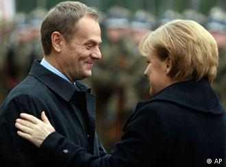 Polish Prime Minister Donald Tusk greets German Chancellor Angela Merkel in Warsaw