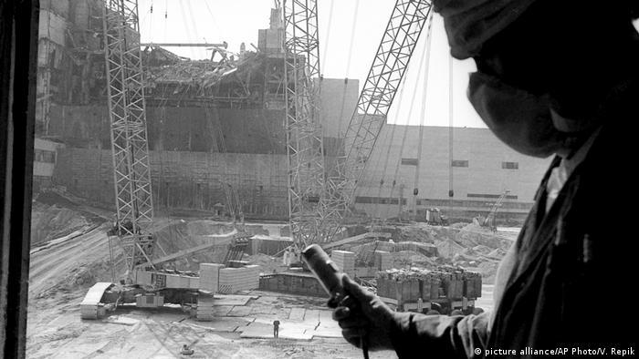 Людина в масці та з дозометром на тлі Чорнобильської АЕС через декілька днів після вибуху в 1986 році