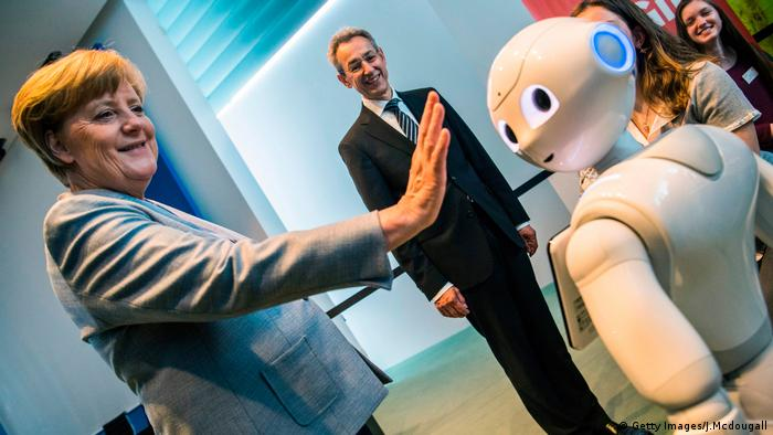 Angela Merkel greets an interactive robot at the Girl's Day fair in the German Chancellery