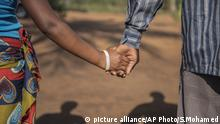 A husband and wife hold hands (picture alliance/AP Photo/S.Mohamed)